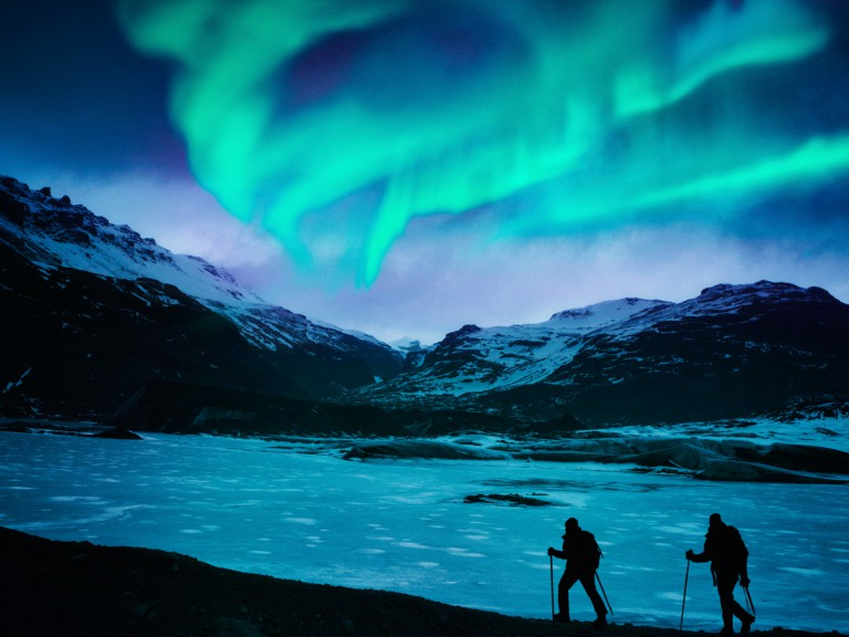travellers viewing nothern lights in snow