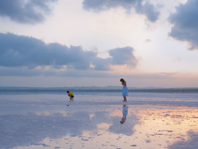 woman and child standing on salt lagoons